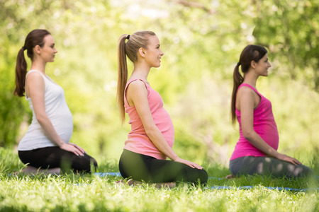 feminity: Three pregnant women relaxing on grass outdoors. Stock Photo