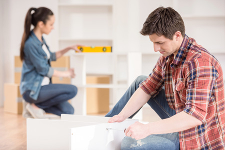 unpacking: Young couple moving in new house. Unpacking boxes and assembling furniture. Stock Photo