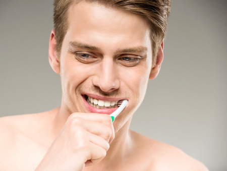 Handsome man cleaning teeth with tooth brush in bathroom. photo