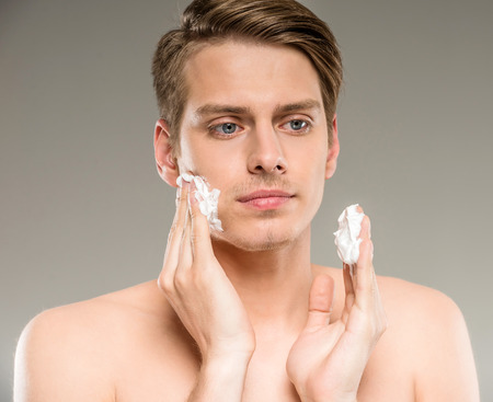 shaving cream: Portrait of a handsome young man is applying shaving cream to his face.