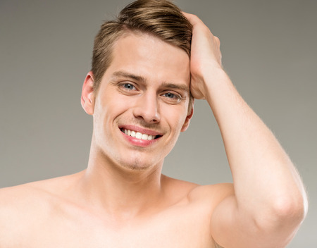man face close up: Young attractive male model posing on grey background. Beauty concept.