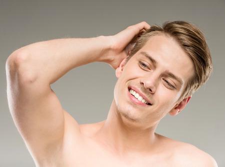attractive male: Modelo masculino atractivo joven que presenta en fondo gris. Concepto de la belleza. Foto de archivo