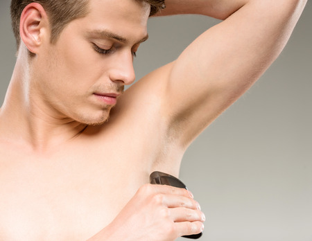 armpit hair: Young handsome man applying deodorant on armpits.