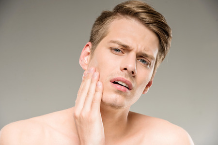 body human skin: Handsome man with pure skin touching his face.