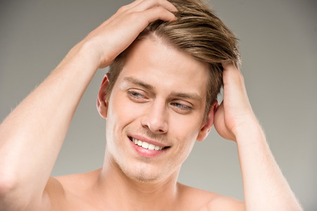 background beauty: Young attractive male model posing on grey background. Beauty concept.