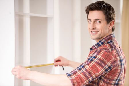 kitchen equipment: Young man measuring home furniture with measure tape. Repair concept. Stock Photo