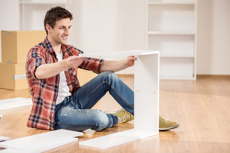 Young man dressed casual assembling furniture in new house.