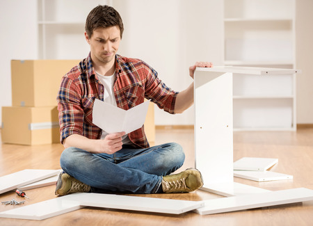 installation: Concentrated young man reading the instructions to assemble furniture in the kitchen at home. Stock Photo