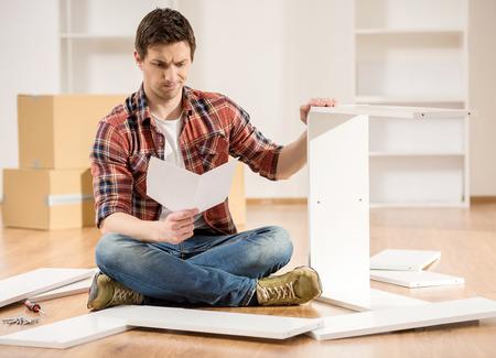 Geconcentreerde jonge man lezen van de instructies om meubels te monteren in de keuken thuis. Stockfoto