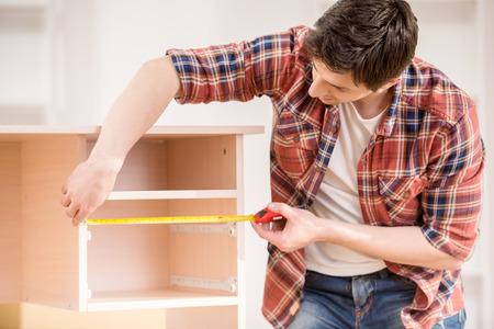constructor: Hombre joven que mide muebles para el hogar con cinta métrica. Concepto de reparación. Foto de archivo