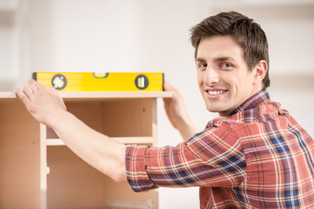 Young man using measure level at home. Repair concept. photo