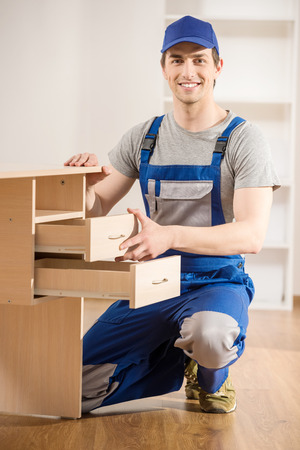 hand tool: Young repairman assembling new table at home interior. Stock Photo