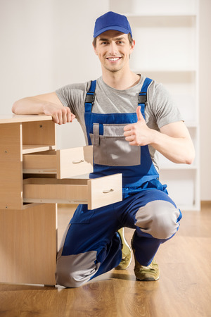 Young repairman assembling new table at home interior. Banque d'images