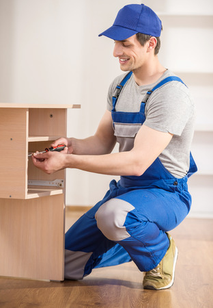 Young repairman assembling new table at home interior. Stockfoto