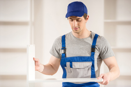 work from home: Young repairman assembling furniture. Home interior. Installation work. Stock Photo