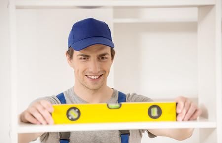 Young smiling repairman using spirit level at home interior. photo