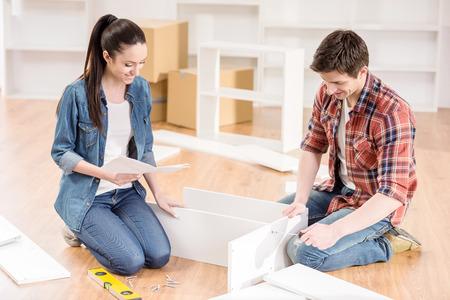 Glückliches Paar Bewegt Sich In Neues Haus. Zusammenbau Von Möbeln. Photo