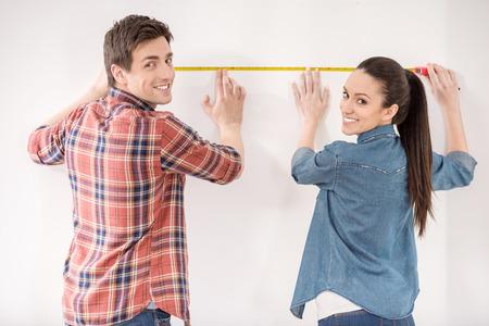 행복 한 젊은 부부 그들의 새로운 빈 아파트를 측정입니다. 수리 및 건물 개념입니다.