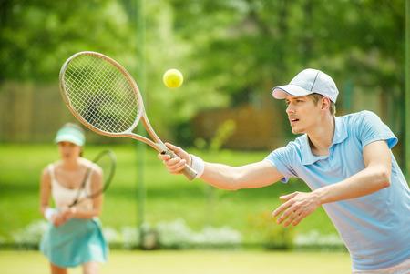 Echtpaar spelen dubbelspel op de tennisbaan. Gezonde levensstijl concept.