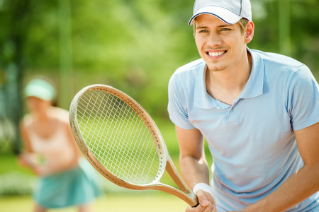 Couple playing doubles at the tennis court. Healthy lifestyle concept. Stok Fotoğraf