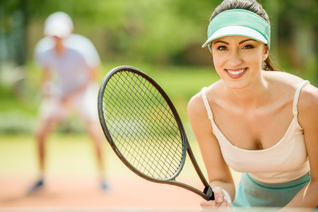 doubles: Couple playing doubles at the tennis court. Healthy lifestyle concept. Stock Photo