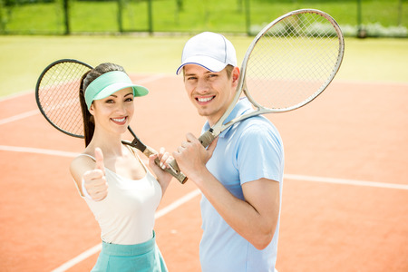 male tennis players: Smiling young couple standing on tennis court, holding tennis racket.