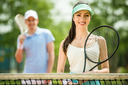 Smiling young couple standing on tennis court, holding tennis racket.