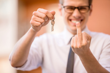 Successful realtor in white shirt showing keys at camera. Stock Photo