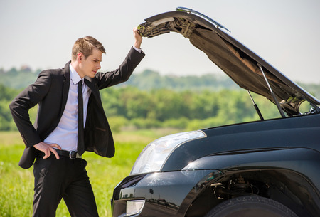 Side view of young businessman examining broken down car engine at countryside. Stock Photo