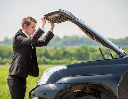 engine bonnet: Side view of young businessman examining broken down car engine at countryside. Stock Photo