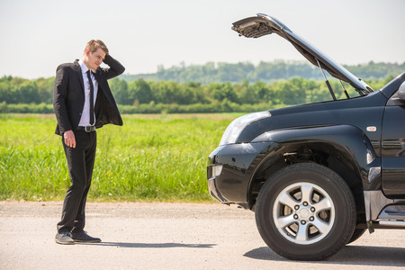 damaged: Full length of businessman with hands on head standing by broken down car at countryside. Stock Photo