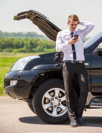 empujando: Hombre joven que tiene problemas con su coche roto, la apertura de la capilla y pidiendo ayuda en el tel�fono celular. Foto de archivo