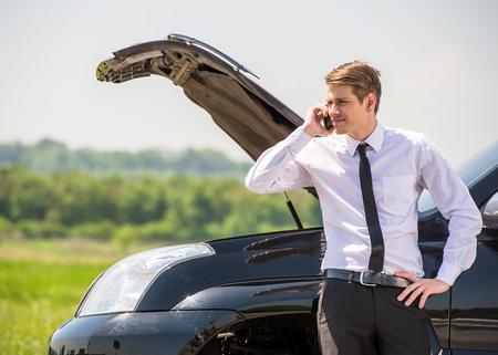 Hombre joven que tiene problemas con su coche roto, la apertura de la capilla y pidiendo ayuda en el teléfono celular.