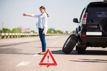 roadside stand: Red warning triangle with a broken down car on the road. Woman catching car. Stock Photo