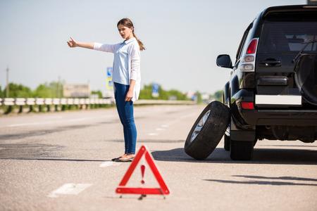 Rode gevarendriehoek met een kapotte auto op de weg. Vrouw vangen auto. Stockfoto