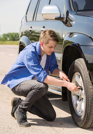 road to change: Young man changing the punctured tyre on his car.
