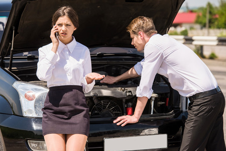 calling for help: Businessman trying to repair his broken car while his woman calling for help on phone. Stock Photo