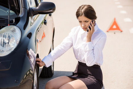 calling for help: Businesswoman sitting near broken car and calling for help on phone. Stock Photo