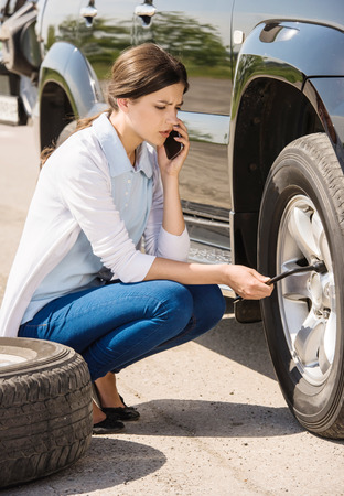 Young woman changing the punctured tyre on his car. Stock Photo