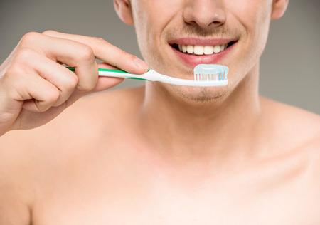 dientes: Hombre guapo limpieza de los dientes con el cepillo de dientes en el baño.