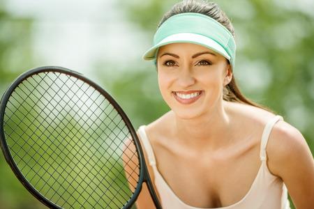 jugando tenis: Hermosa chica deportiva jugando tenis muy apasionadamente. Foto de archivo
