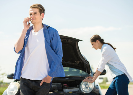 calling for help: Young man standing near broken car and calling for help on phone.