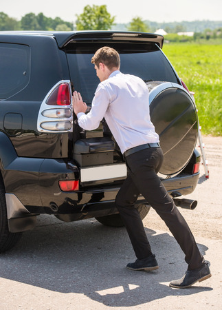 empty tank: Young businessman pushing a car with empty fuel tank. Stock Photo