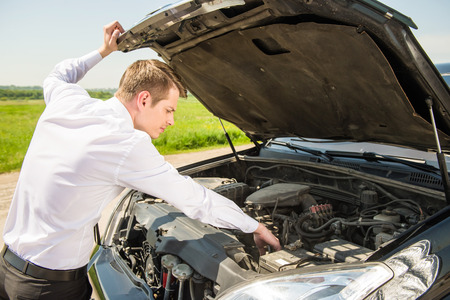 engine: Side view of young businessman examining broken down car engine at countryside. Stock Photo