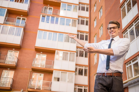 young executive: Young successful realtor welcomes to new living block.