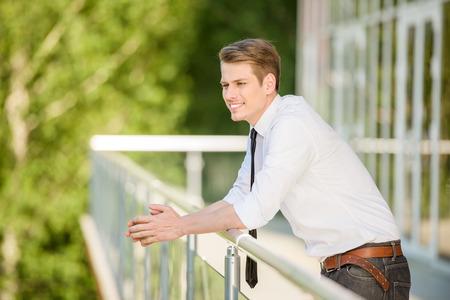 El hombre joven se vistió de descanso oficial en balcón de la oficina. Foto de archivo