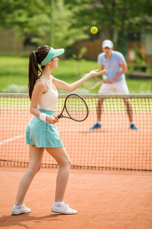 Cheerful young woman playing tennis with boyfriend outdoors.