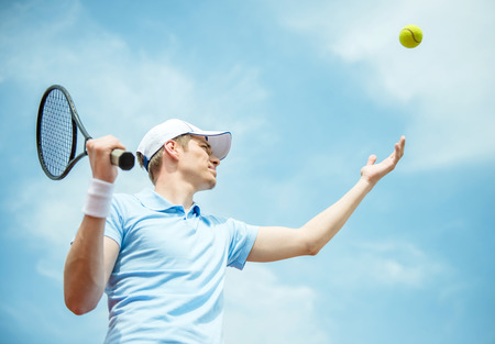 Handsome tennis player on hard court serving the ball. Stock Photo