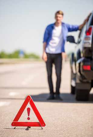 roadside stand: Red warning triangle with a broken down car on the road. Stock Photo