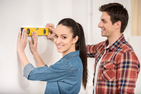 Smiling couple doing repair at home using spirit level to measure. photo